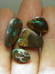 Close up of 3 $25 polished Boulder Opals